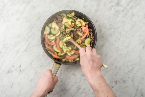 Bak de courgette, het gehakt en de tomaat.