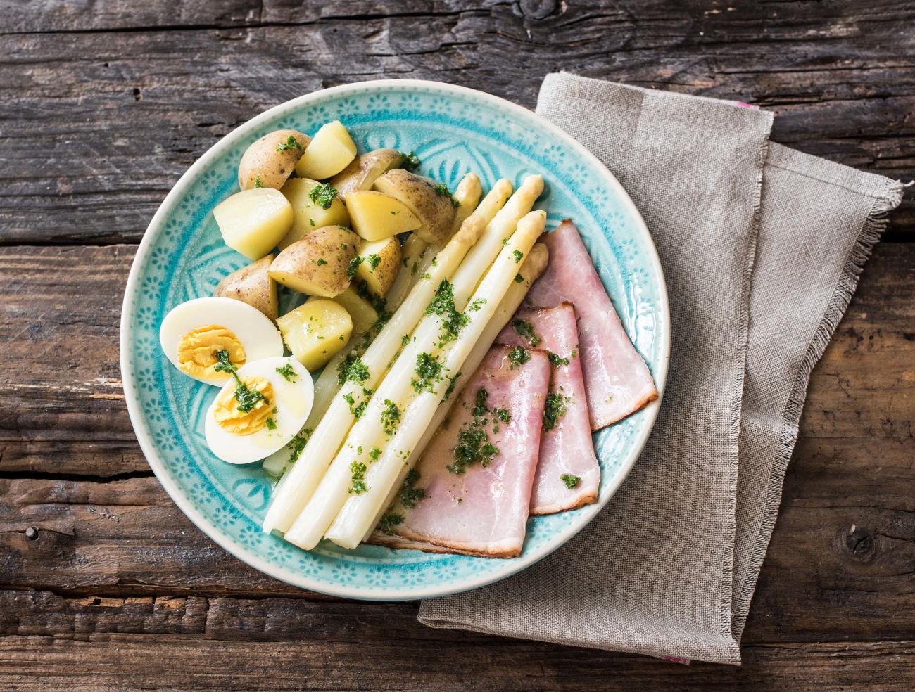 Witte asperges met achterham, gekookt ei en peterselie