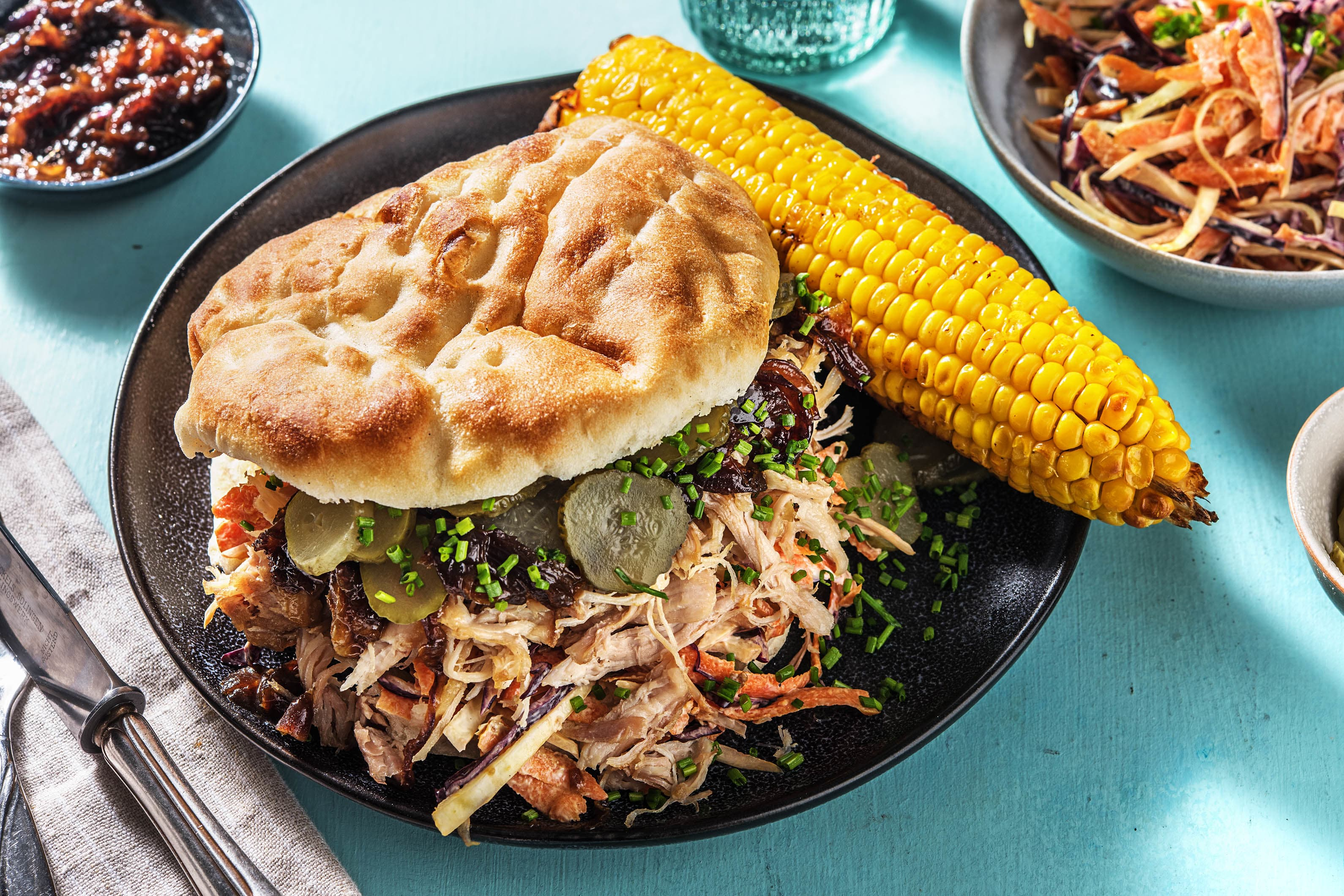 Pulled chicken met coleslaw, maiskolf en augurk