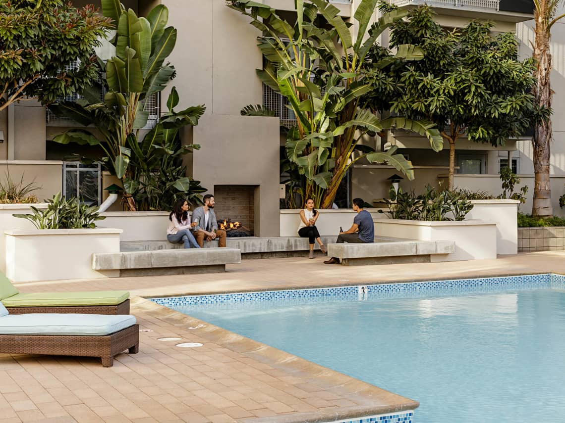 A group of friends lounging poolside at 550 Moreland apartments in Santa Clara, CA