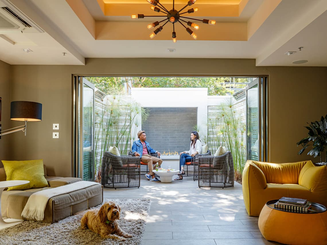A couple and dog enjoying an indoor/outdoor recreation area at Shadowbrook apartments in Sunnyvale, CA