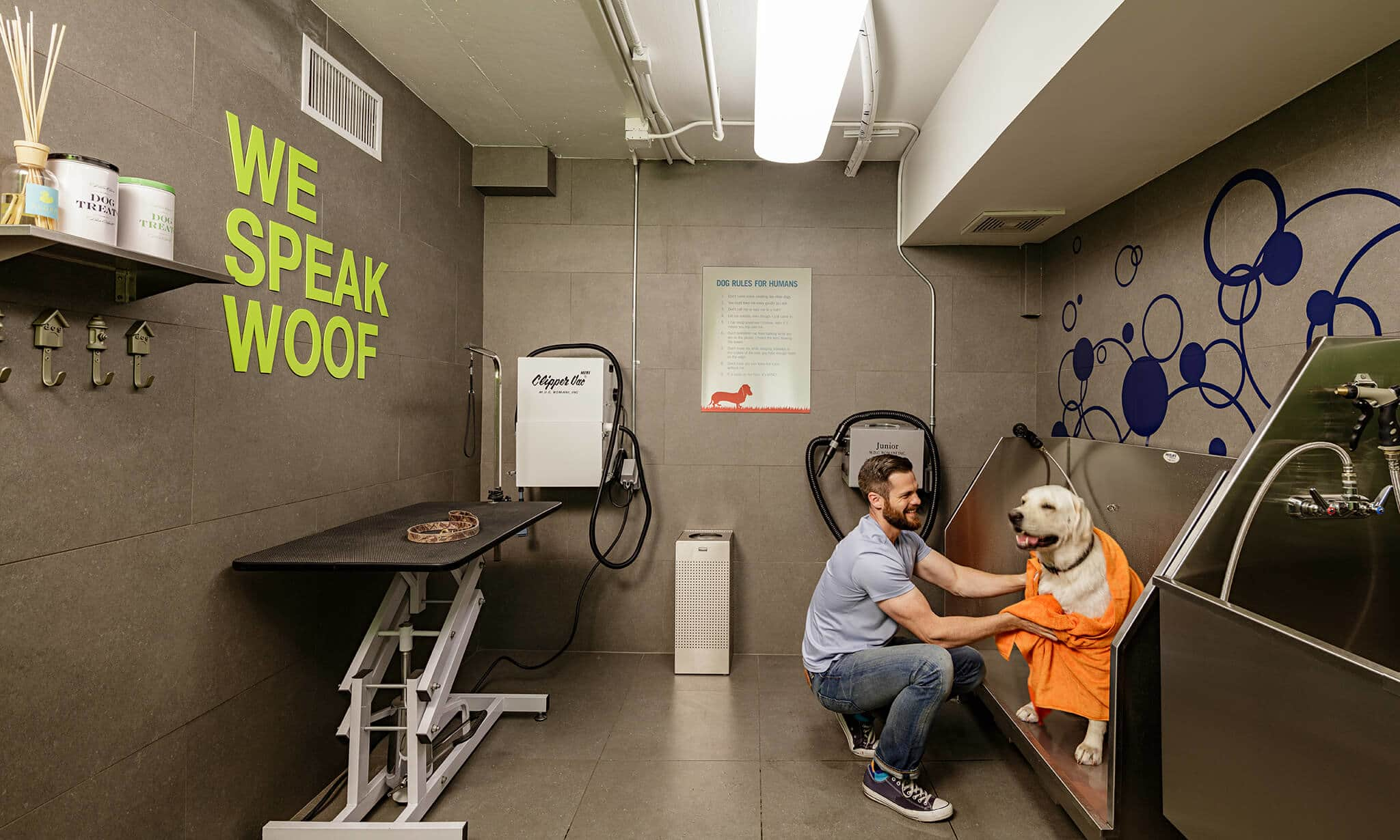 A man washing his dog in an apartment pet wash station, showing how home is efforltess