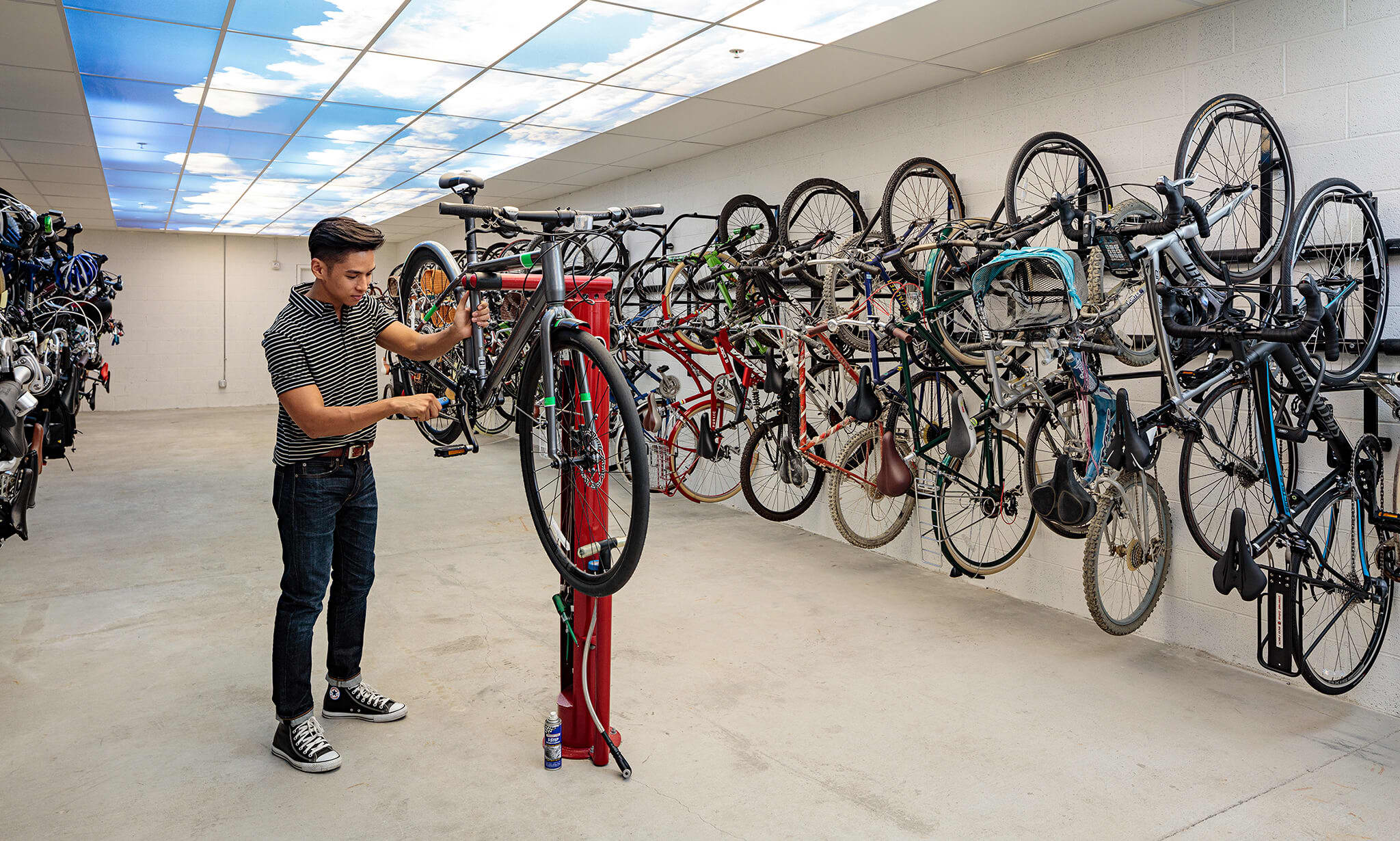 A young man fixing his bicycle in an indoor bicycle room
