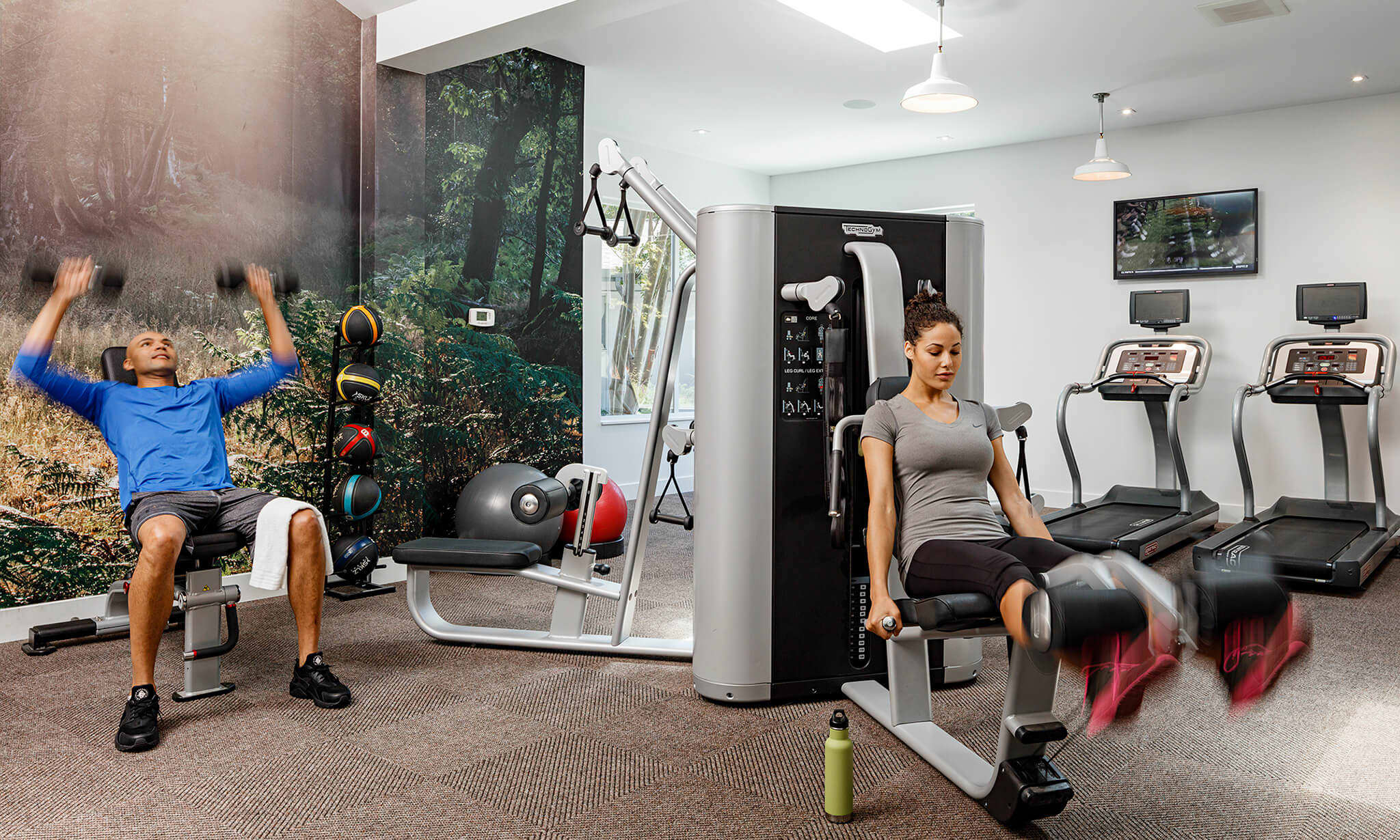 A man and woman exercising in an apartment fitness center