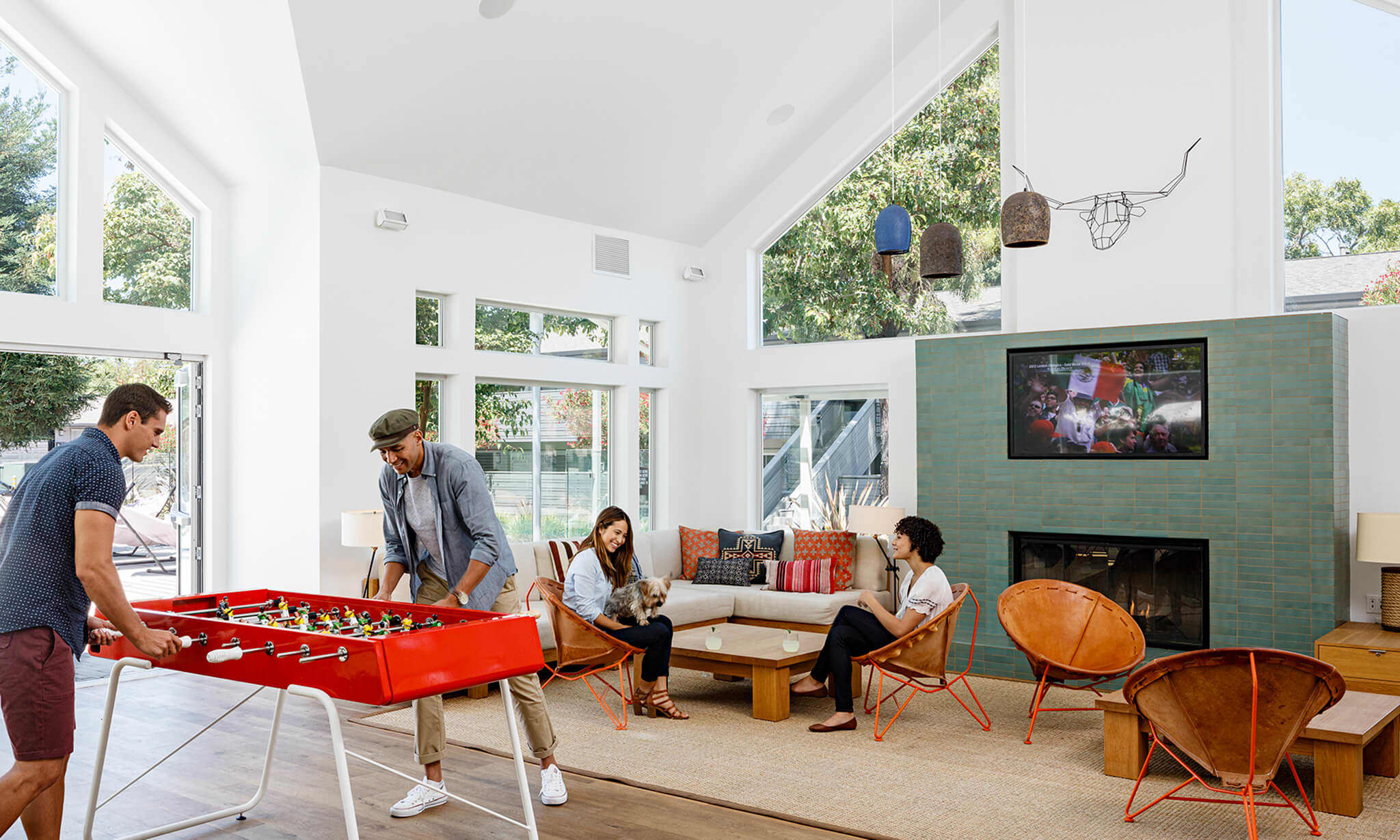 Two people playing Foosball while another two lounge by a fireplace