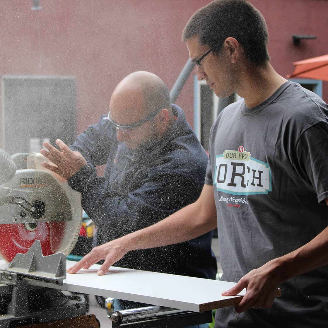 Two men cutting a piece of wood while wearing safety goggles