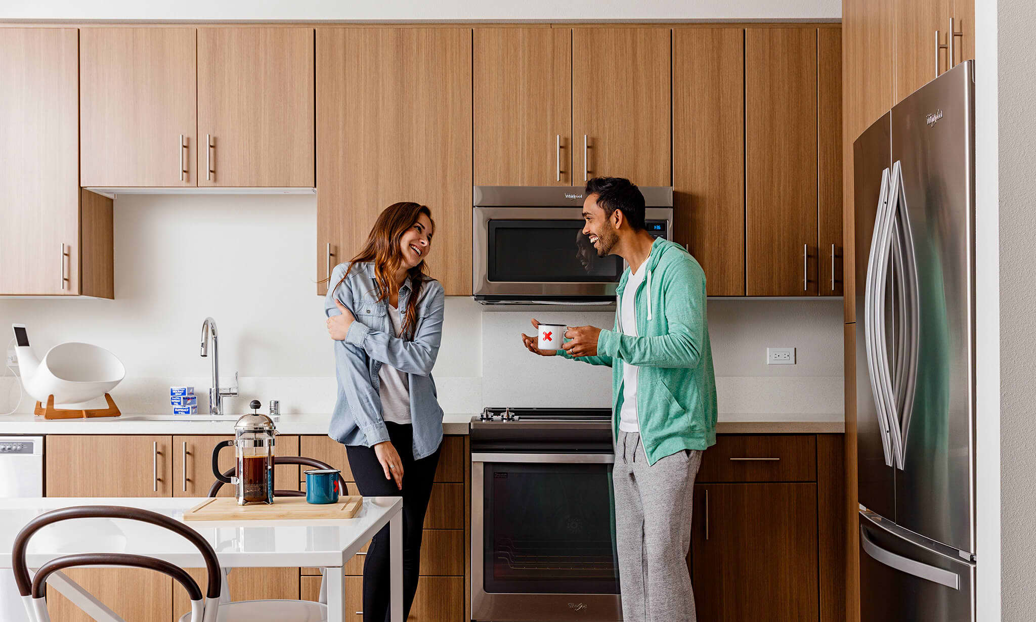 A couple laughing in an apartment kitchen, showing how home is personal.