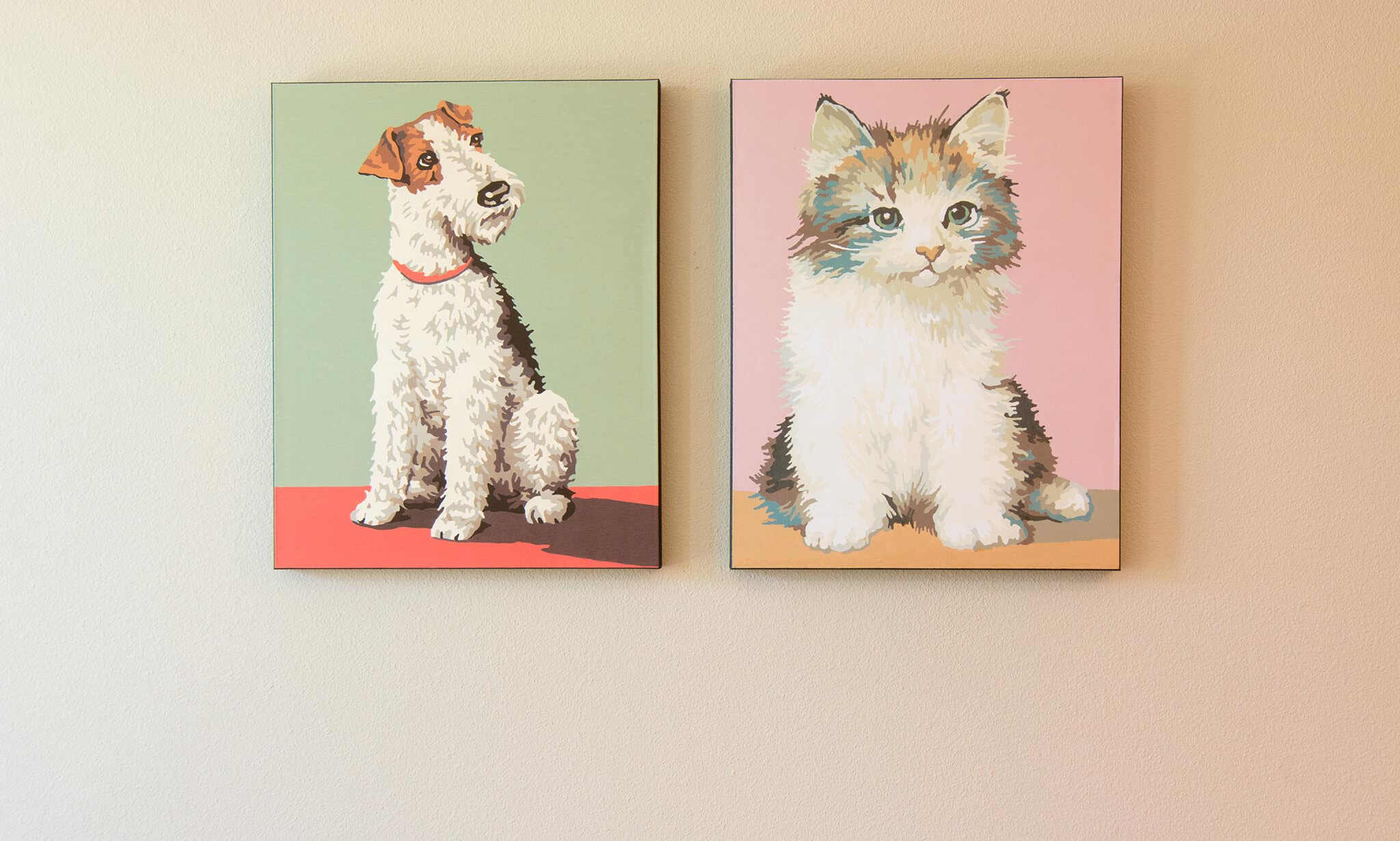 Two framed illustrations, one of a dog and one a cat done in pastel colors