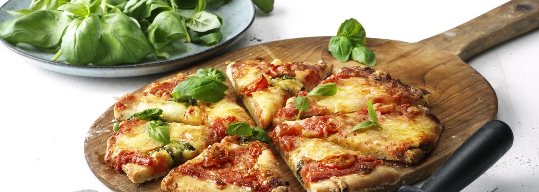 Glutenfri pizza på en bräda, bredvid står en tallrik med basilika