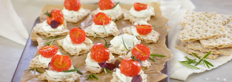 Glutenfria knäckesnittar med tomat och färskost på en träbricka