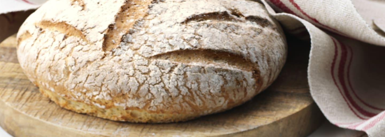 Stort ljust glutenfritt bröd på en träbräda