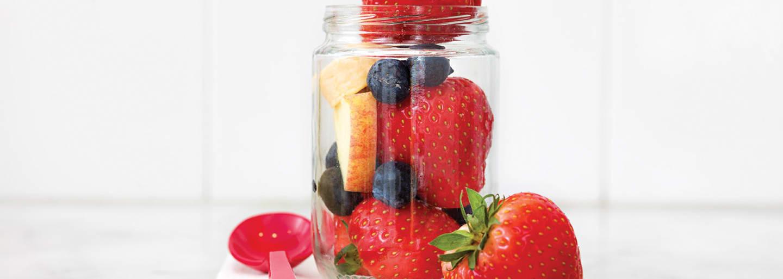 mansikoita, mustikoita ja omenaa lasissa