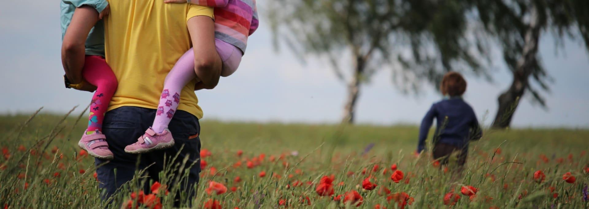 Pappa och barn på fält med vallmo