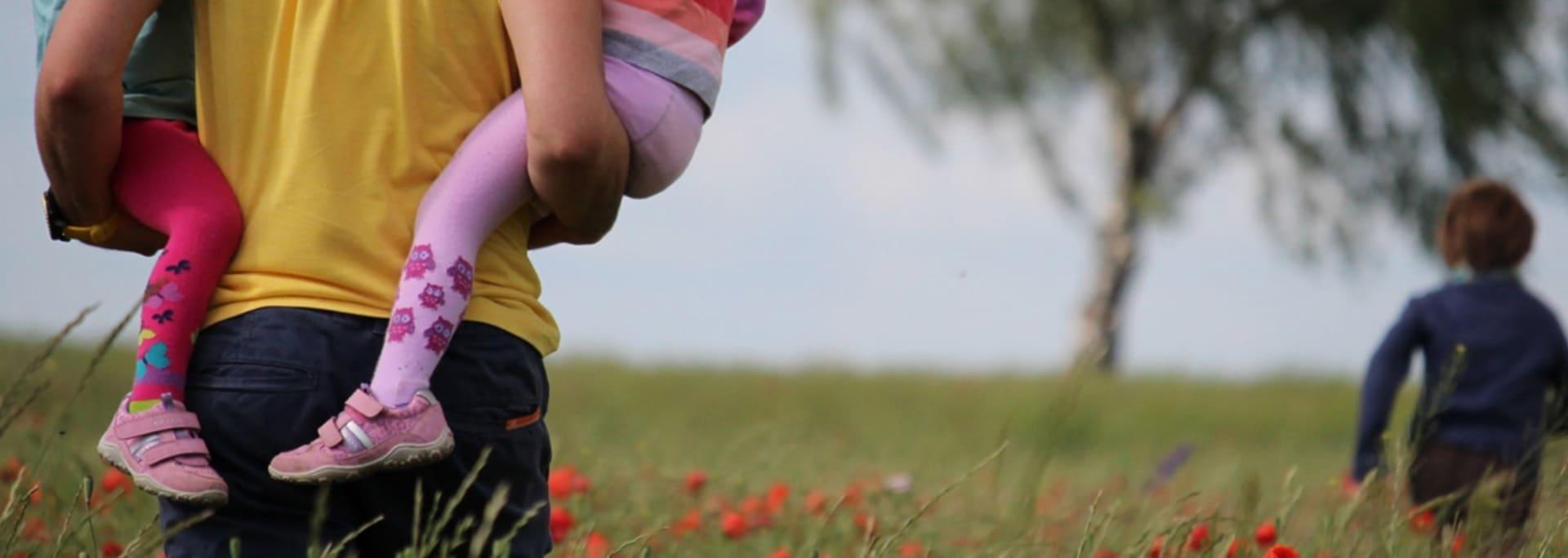 Pappa på vallmofält med barn