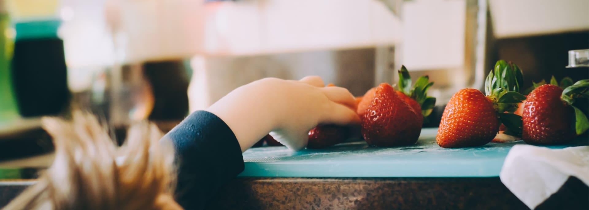 Barn sträcker sig efter jordgubbarna i köket