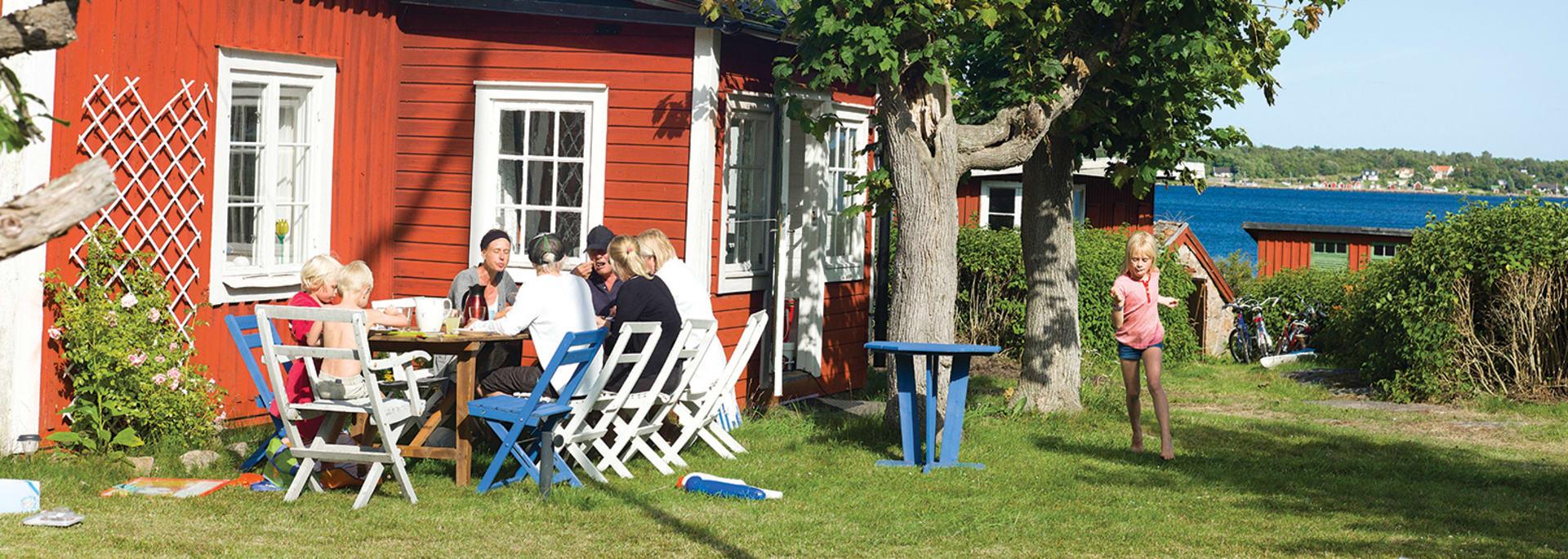 Familj äter frukost vid sommarstugan en solig sommardag
