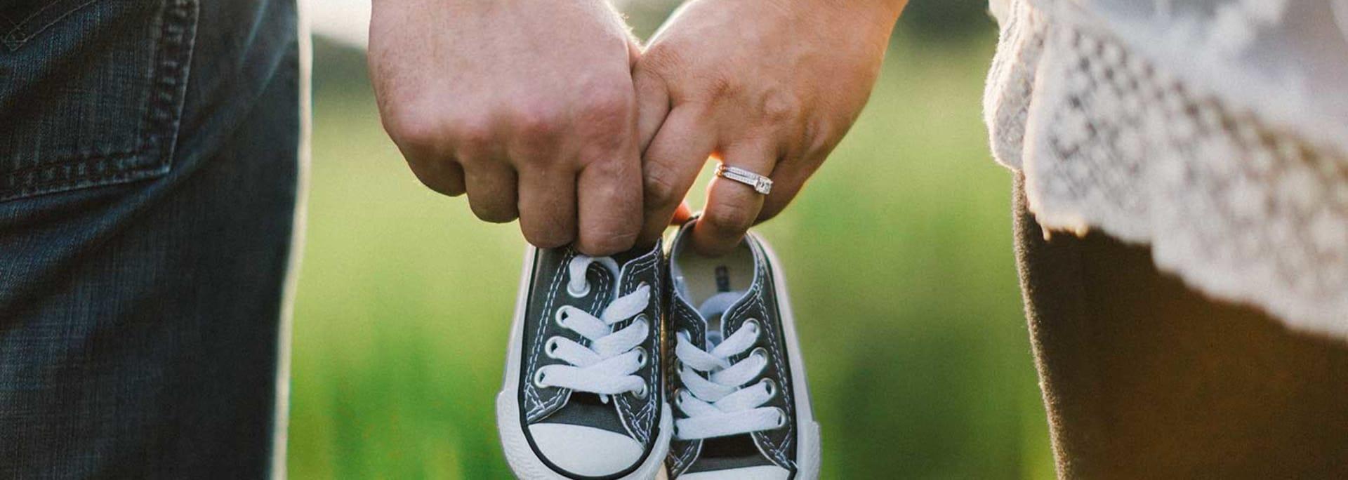 Föräldrar gravida, håller babyskor i handen