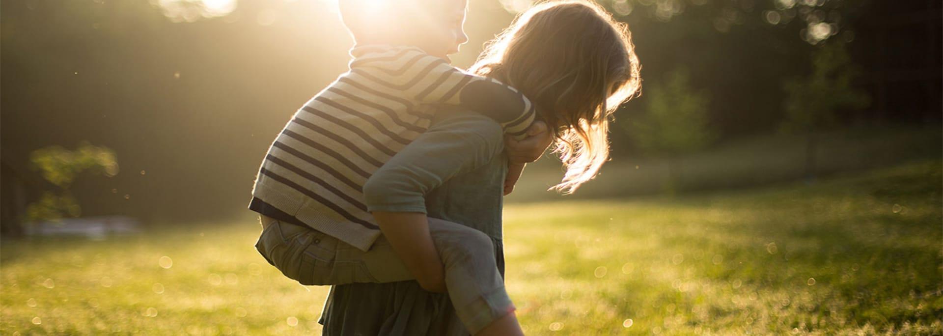 Två barn leker på äng en sen sommardag