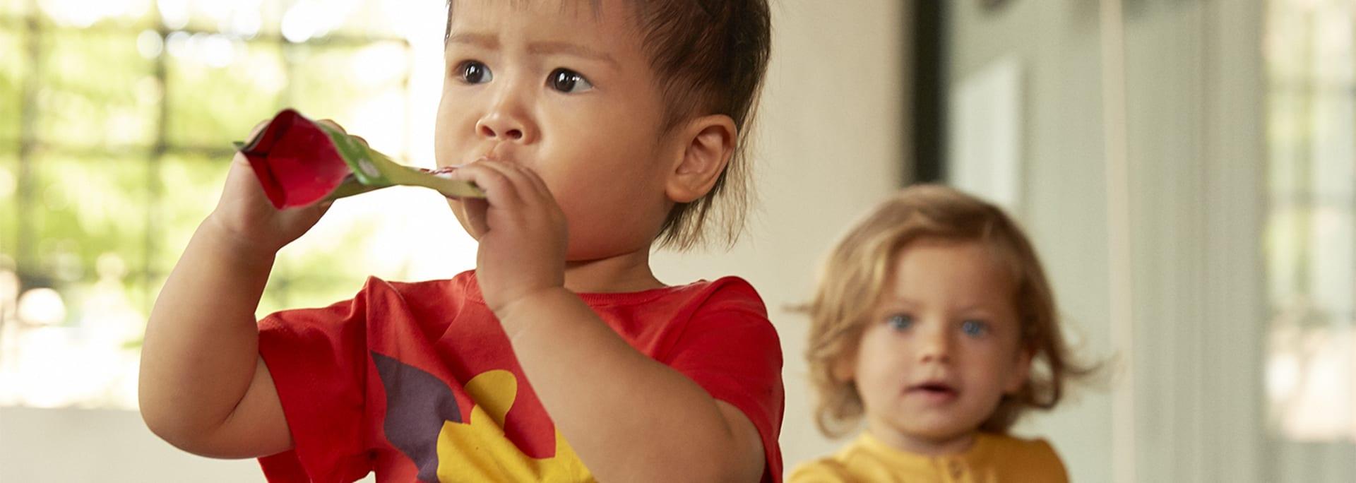 Et barn spiser fra en klemmepose