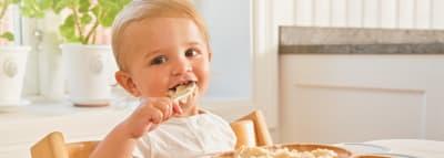 BArn äter Oat bowl mellanmål vid ett bord