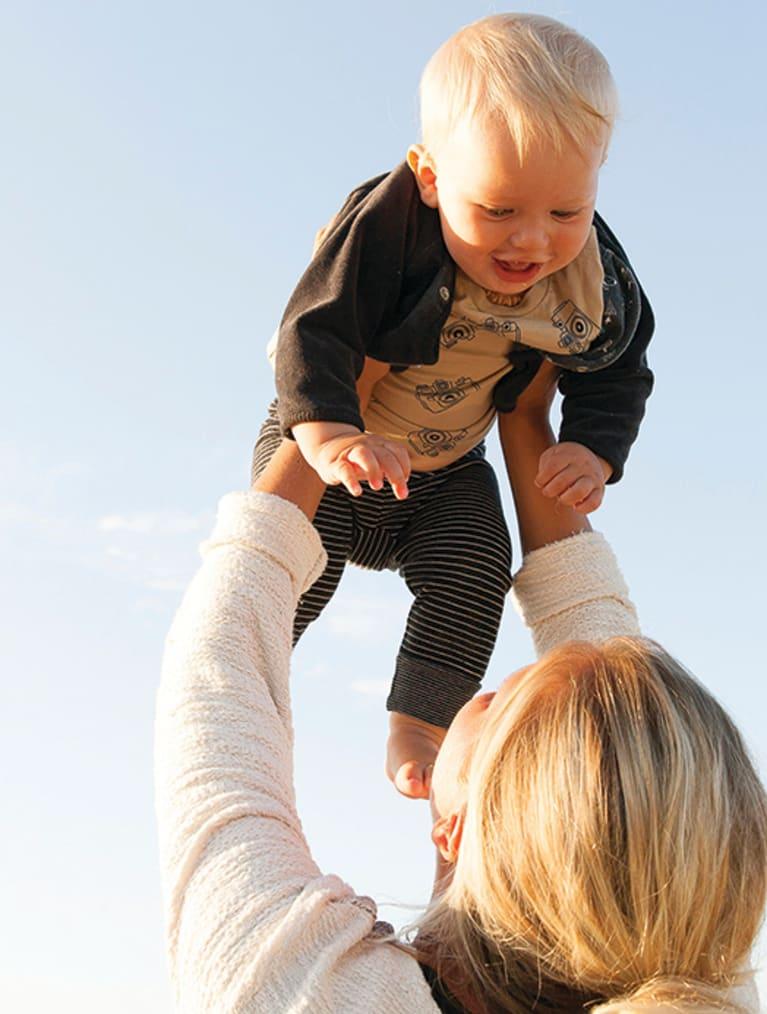 Miljöbild på mamma som lyfter upp sitt barn