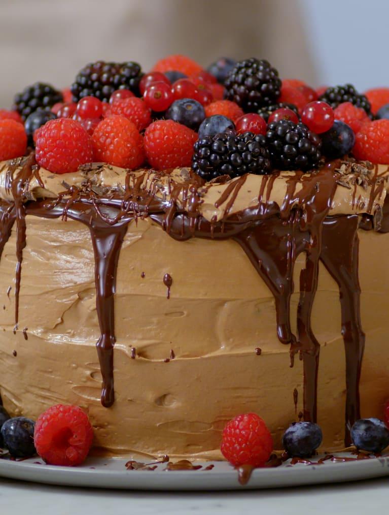 En hög glutenfri chokladtårta toppad med smält choklad, hallon och blåbär