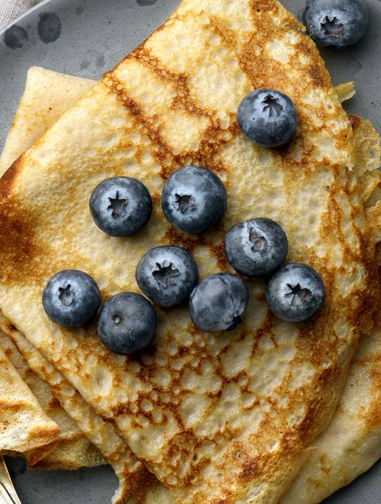 Två vikta glutenfria pannkakor på en en blå tallrik, toppade med blåbär