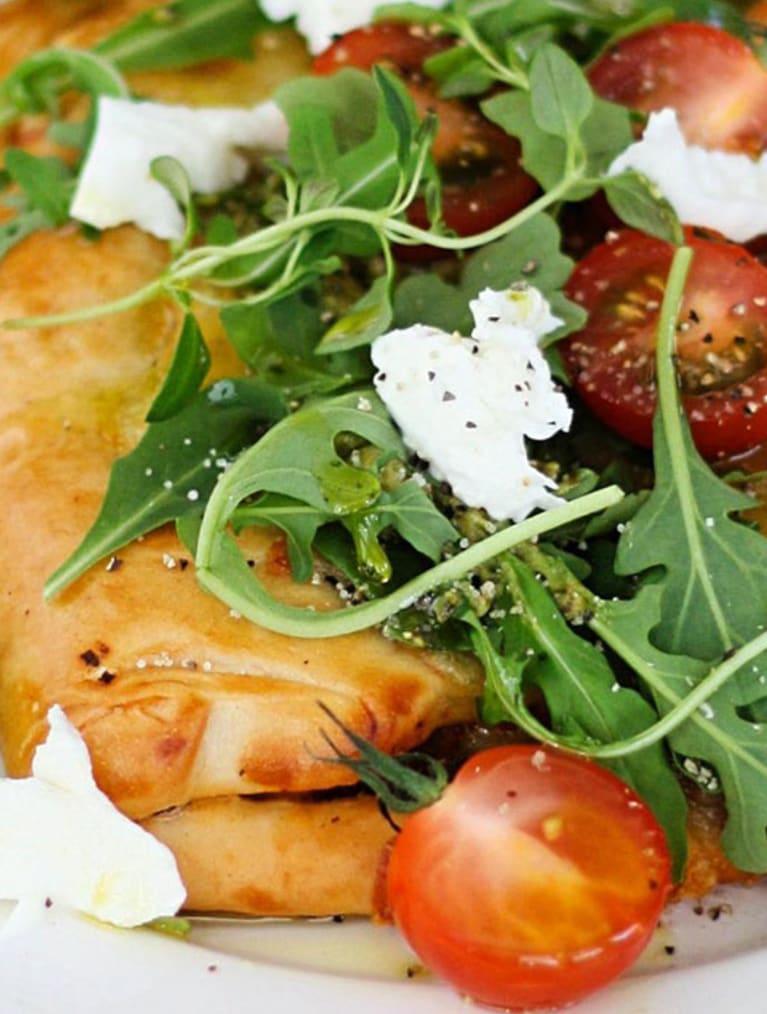 Glutenfri pirog toppad med sallad, tomat och fetaost