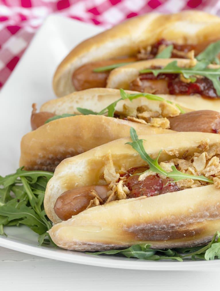Hotdogeja lautasella ja punainen ruutuliina