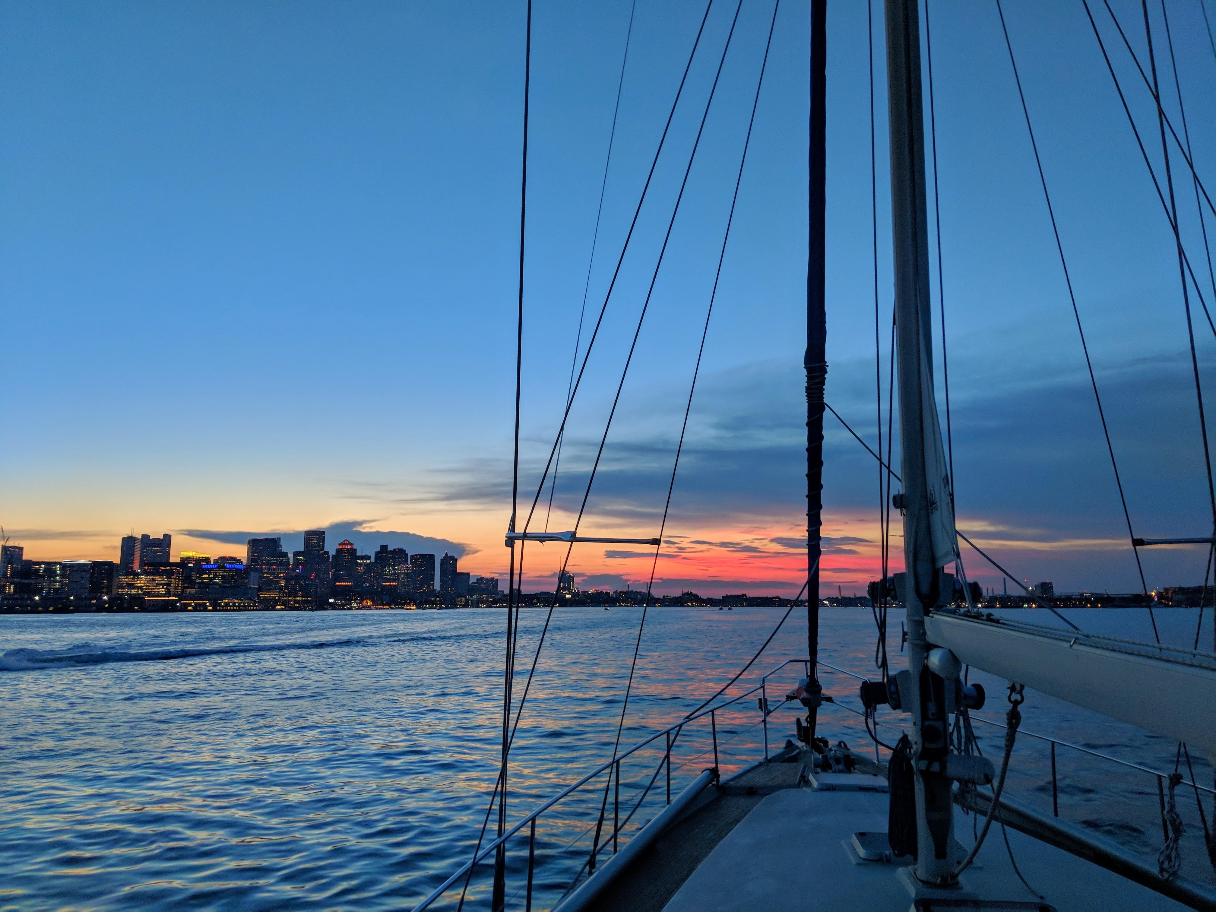 A sailboat approaching Boston at sunset