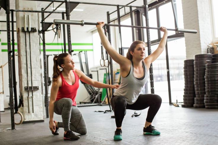 Tren med personlig trener. PT og kvinne med vektstang