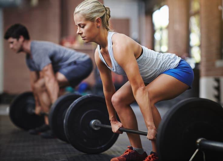 Kvinne og mann med vektstang. Styrketrening