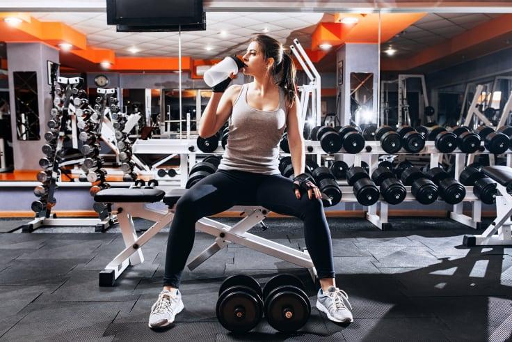 Kvinna som dricker proteinshake på gym