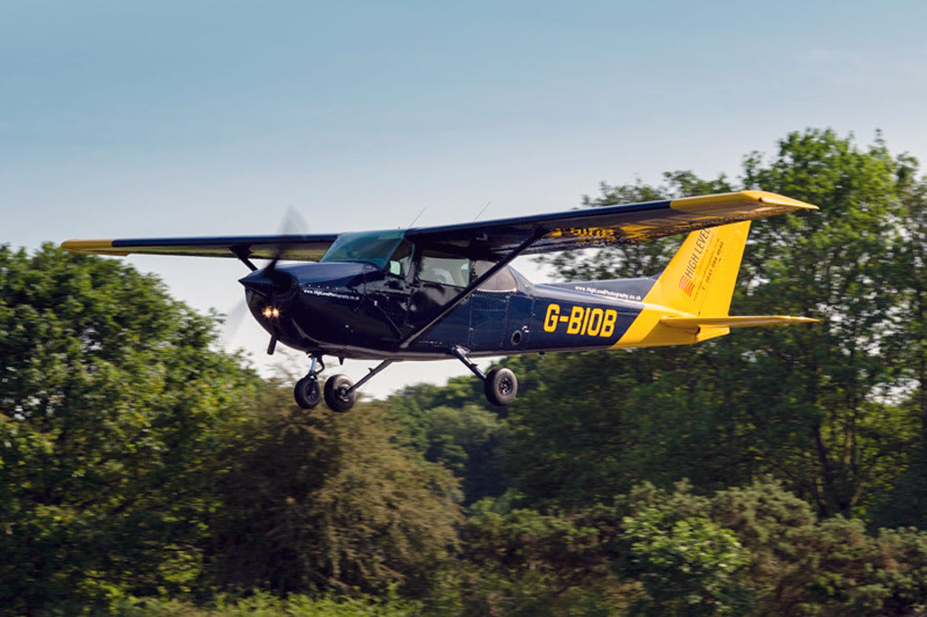 A blue an yellow Cessna 172 light aircraft flying in front of woodland