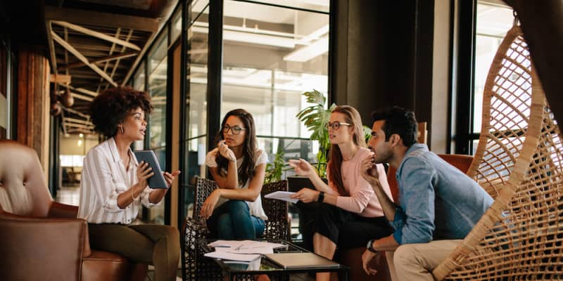 group of young professionals having a casual meeting around a coffee table