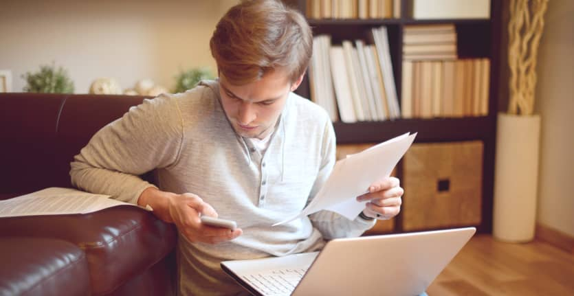 A young man in a light sweatshirt and jeans leans against a leather couch while poring over papers, a laptop, and a smartphone.