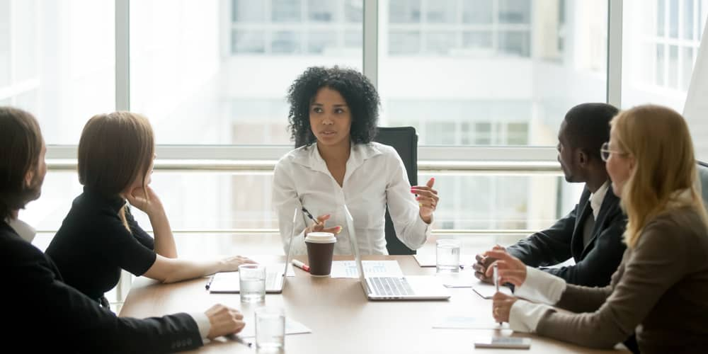 A business executive leads a lively discussion with her coworkers in a brightly lit conference room.
