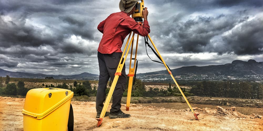 A man in a cowboy hat and technical pants stands before a wide-open valley, fiddling with the controls on a surveying device.