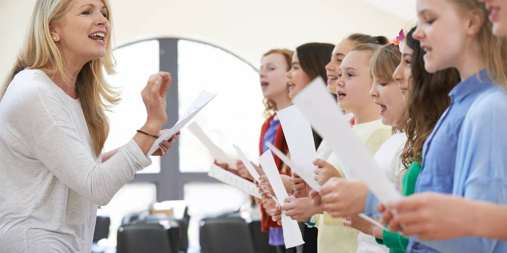 A music treacher leads the practice session for middle school chorus.