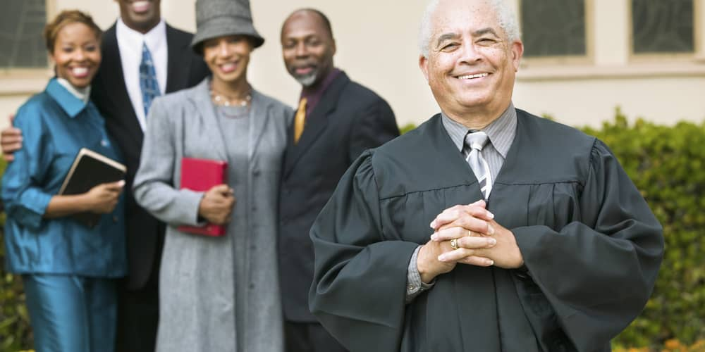 A pastor stands smiling in front of a church and well-dressed members of its congregation.