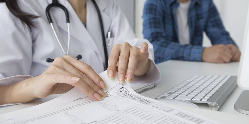 A medical records specialist double-checks the information on a printed file against records on a computer, while a patient sits nearby.