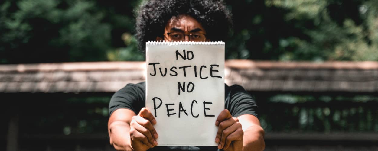 Image of a Black person holding a sign reading 'No Justice No Peace'