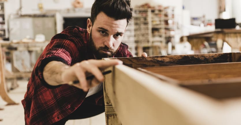 A bearded man in a workshop wearing a flannel shirt eyes a table he's restoring.