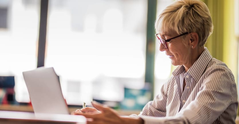 A woman with short, gray hair in an Oxford shirt and glasses looks down at her laptop computer, pen in hand.