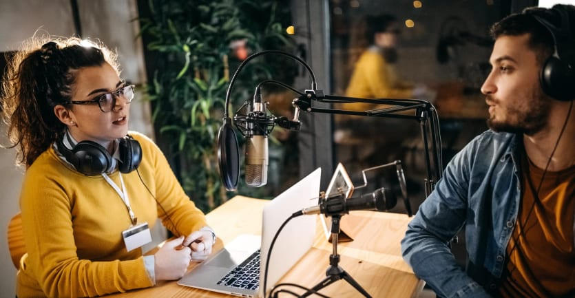 A man and woman with headphones sit at a table covered with a laptop, microphones, and other podcast equipment as they hold an earnest discussion.