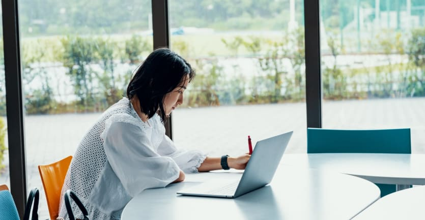 A woman in a white blouse sits with her laptop at a conference table positioned in front of floor-to-ceiling windows in a building on a college campus.