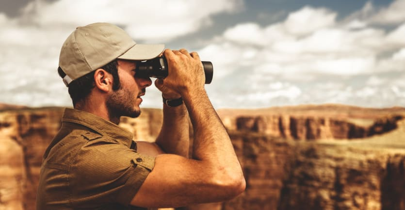A young park ranger looks through binoculars at the vast landscape of the Grand Canyon.
