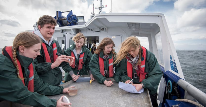 Marine biologist students wearing life jackets sit together on a boat to inspect plankton samples.