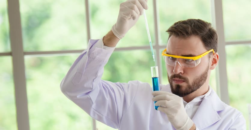 A scientist wearing gloves and safety glasses analyzes a blue liquid in a test tube.