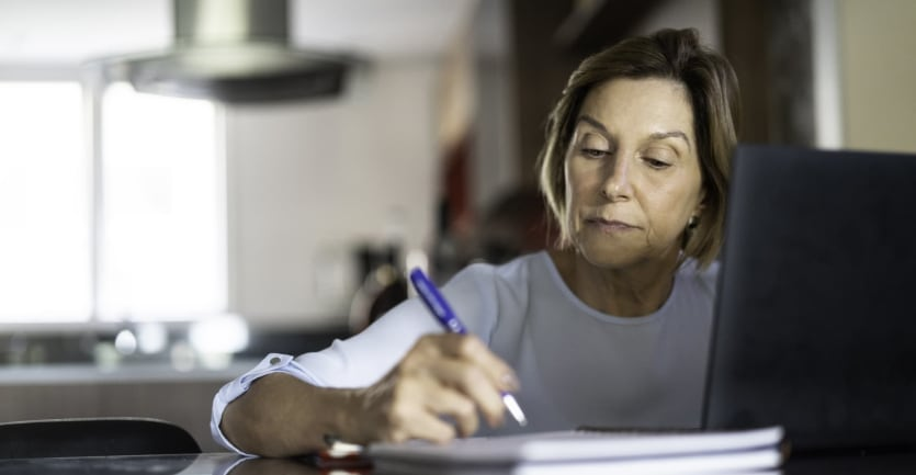 A middle-aged woman sits at a table, her laptop in front of her, and takes notes in a notebook.